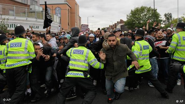 British police officers try to control anti-fascist protesters as they charge against anti-Muslim demonstrators