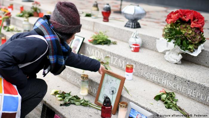 A woman lays a flower at a memorial to the victims of the 2016 Christmas market attack in Berlin, Germany (picture alliance/dpa/B. Pedersen)