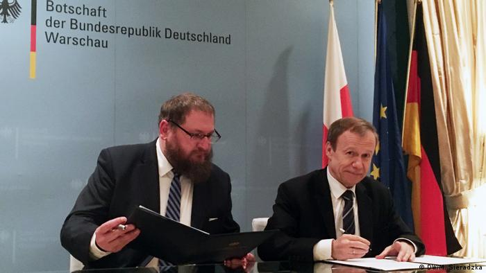 Polish and German representatives signing a cooperation agreement for the Sobitor concentration camp memorial