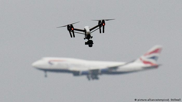 Voo de um drone e, no fundo, um avião em processo de pouso no aeroporto de Gatwick, em Londres