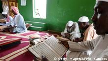 Muslims read a Quran after a Friday prayer on May 18, 2018 at a mosque in Abidjan during the holy month of Ramadan. (Photo by Sia KAMBOU / AFP) (Photo credit should read SIA KAMBOU/AFP/Getty Images)