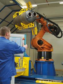 Рабочий обслуживает промышленного робота