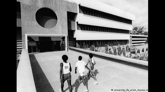 Black and white photo shows three youths in sports attire walking toward a building in geometric contours (university_ife_arieh_sharon, bauhaus100.de)