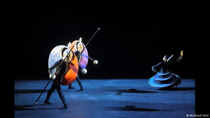 Dancers onstage striking contorted poses and wearing absurd, colorful, geometrically-shaped costumes in the form of disks and spirals (Winfried Hösl)
