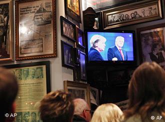 People watch the TV debate in a bar
