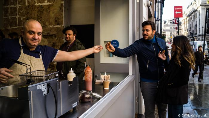 Imad Alarnab hands a falafel to a couple who walk by his pop-up restaurant (DW/M. Karakoulaki)