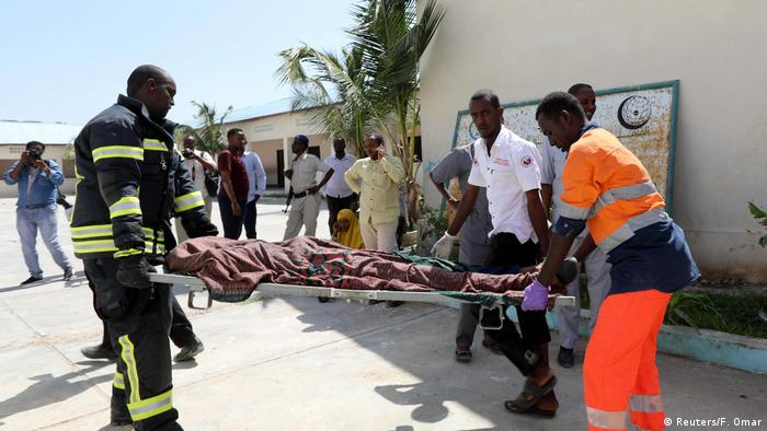 Rescuers carry the death body of an unidentified man killed following an explosion near president's residence in Mogadishu