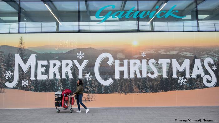 Passagierin mit Gepäck vor Schild Merry Christmas (Foto: Imago)