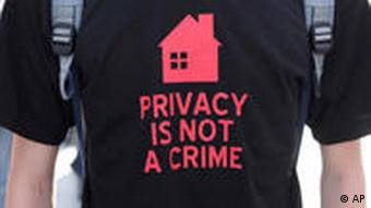 Person wearing a black shirt with a red house and the words Privacy is not a crime