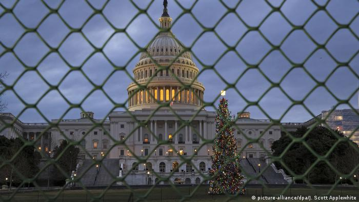 US Capitol building at night on the other side of a chain-link fence