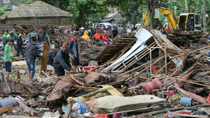 Pessoas inspecionam destroços de casas após chegada de tsunami na Indonésia