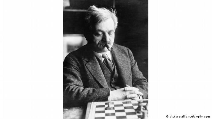 Emanuel Lasker mit Zigarre im Mund am Schachbrett sitzend.