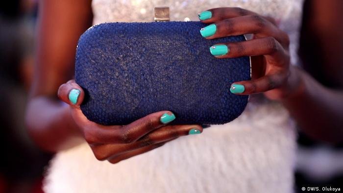 A model holding a blue clutch purse made of fish skin at a fashion show in Lagos, Nigeria (DW/S. Olukoya)