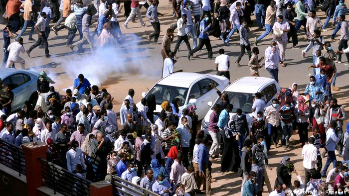Sudanese demonstrators run from teargas lobbed to disperse them as they march along the street during anti-government protests in Khartoum.