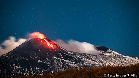 Italy | Mount Etna at night with lava and molten rock emerging from the volcano under a starry sky