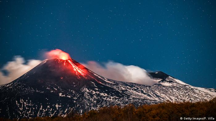 Italy   Mount Etna at night with lava and molten rock emerging from the volcano under a starry sky