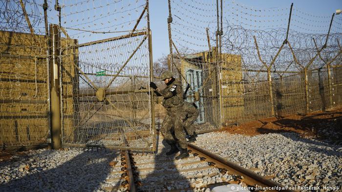Ein südkoreanischer Soldat öffnet innerhalb der entmilitarisierten Zone über den Gleisen die nach Nordkorea führen ein Tor. (picture alliance/dpa/Pool Reuters/K. Hong-Ji)