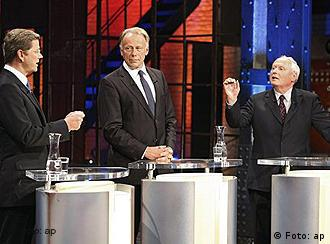 The three opposition candidates stand behind podiums in a TV studio