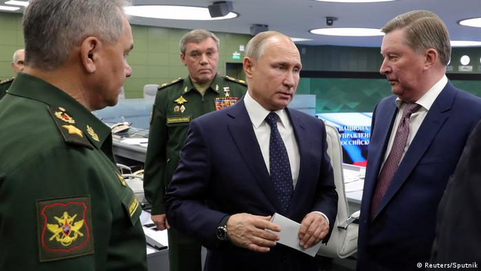 Russia's President Vladimir Puting, center, speaks with Defence Minister Sergei Shoigu, center, and Special Presidential Representative for Environmental Protection, Ecology and Transport Sergei Ivanov.