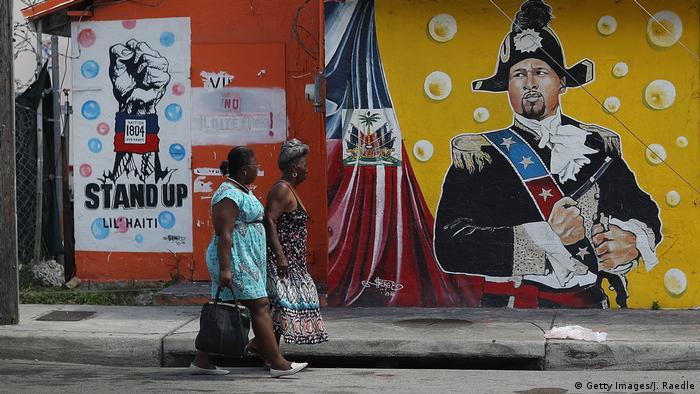 Women walk past a colorful mural in Miami's Little Haiti neighborhood
