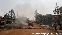 27.12.2018***in Beni People walk by a burning tyres, on December 27, 2018 in Beni, eastern Democratic Republic of Congo, after a demonstration of thousands of people protesting against the postponement, announced the day before by the Congolese national committee, of the general elections in this area because of the Ebola outbreak and the mass killings of civilians in this trouble part of DRC. - Already postponed three times, the elections are due to bring the curtain down on the era of President Joseph Kabila, in charge of the vast mineral-rich country for nearly 18 turbulent years. (Photo by Alexis HUGUET / AFP) (Photo credit should read ALEXIS HUGUET/AFP/Getty Images)