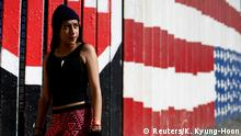 Cristhy Alexandra Ortiz, a migrant from Honduras, part of a caravan of thousands traveling from Central America en route to the United States, poses in front of the border wall between the U.S. and Mexico in Tijuana, Mexico, November 23, 2018. REUTERS/Kim Kyung-Hoon SEARCH KYUNG-HOON DREAMS FOR THIS STORY. SEARCH WIDER IMAGE FOR ALL STORIES.