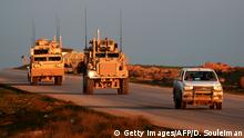US Marine Corps tactical vehicles are escorted by a Syrian Democratic Forces (Getty Images/AFP/D. Souleiman)