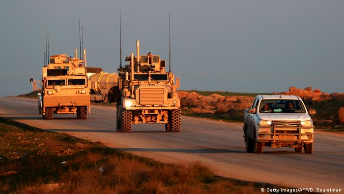 US Marine Corps tactical vehicles are escorted by a Syrian Democratic Forces