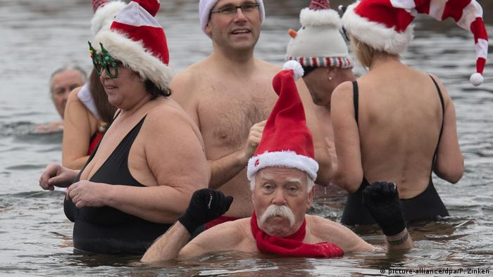 People in a lake with Santa Claus costumes