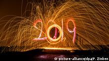 27.12.2018, Berlin: Mit einer Taschenlampe zeichnet ein Mann die Jahreszahl 2019 in den Abendhimmel auf einem Feld in Mahlsdorf, während hinter ihm ein Mann brennende Stahlwolle durch die Luft schleudert (Aufnahme mit Langzeitbelichtung). Foto: Paul Zinken/dpa +++ dpa-Bildfunk +++ | Verwendung weltweit
