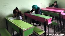Photo for children going back to school in Raqqa after ISIS The photo says that children are sitting on their desks and writing The photos taken by Reem Alnasser , Raqqa, 25.12.2018