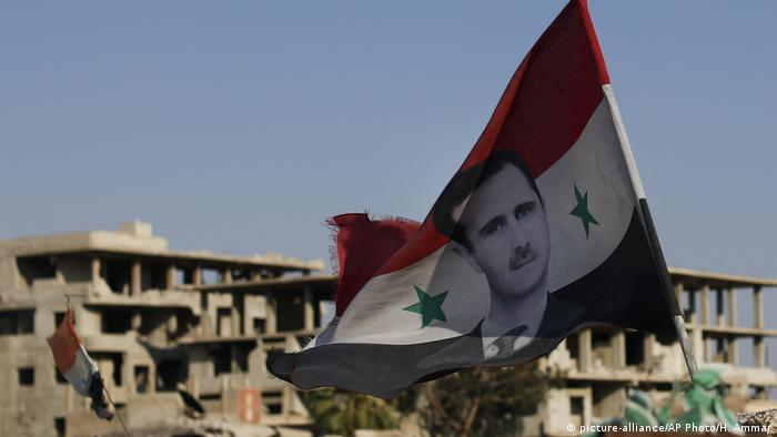 Syrian flag with picture of Assad (picture-alliance/AP Photo/H. Ammar)