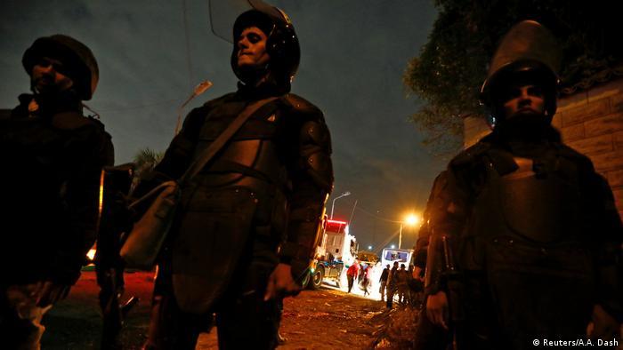 Três policiais egípcios, munidos com capacetes, de prontidão diante de rua, na penumbra, interditando área de atentado em Gizé