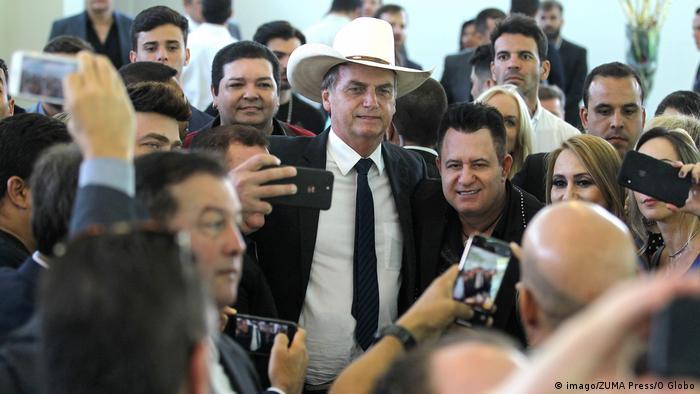 Bolsonaro, de terno, gravata e chapéu de vaqueiro, em meio a apoiadores