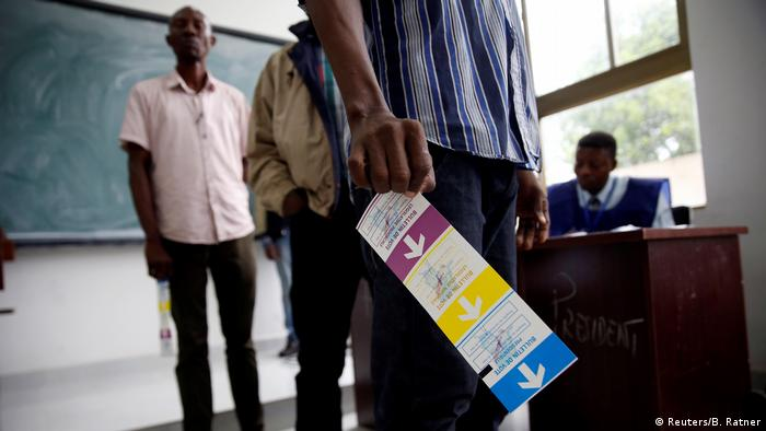Men wait in line to cast their vote at a polling station in Kinshasa
