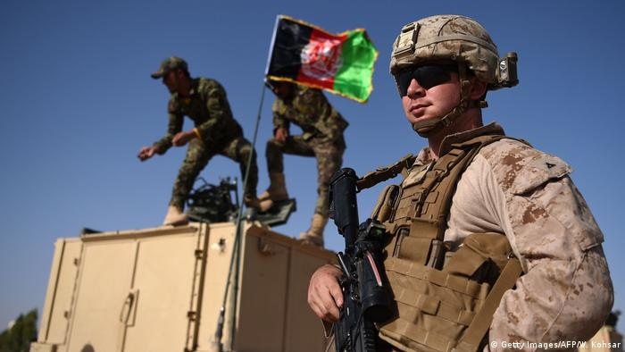 A US marine in front of an armed vehicle watching as Afghan soldiers raise the Afghan flag