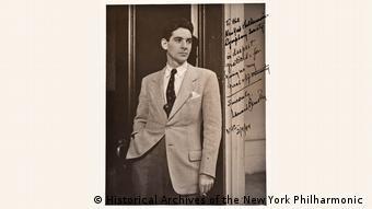 Leonard Bernstein lehnt rauchend an einem Türrahmen.