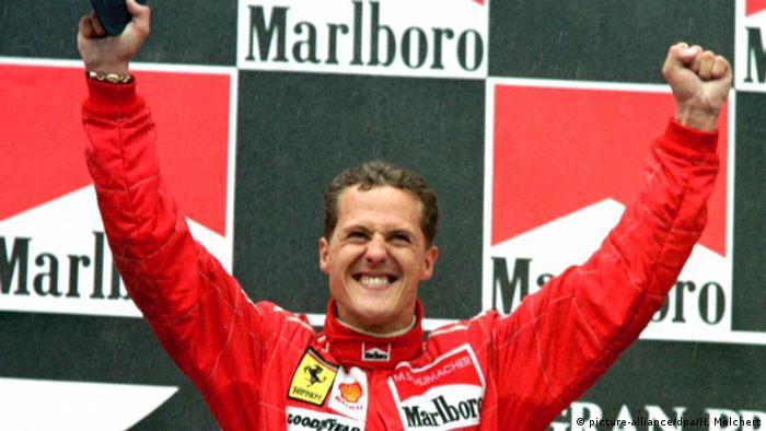 Schumacher, com uniforme de piloto, com os dois braços levantados num momento de comemoração