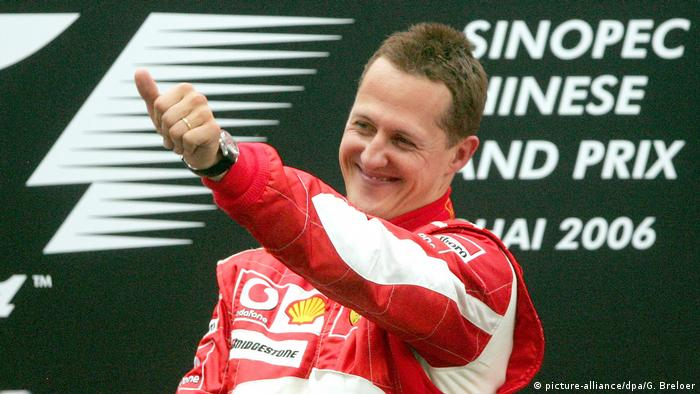 Sorridente e com macacão vermelho da Ferrari, Schumacher ergue o braço esquerdo e faz sinal de positivo