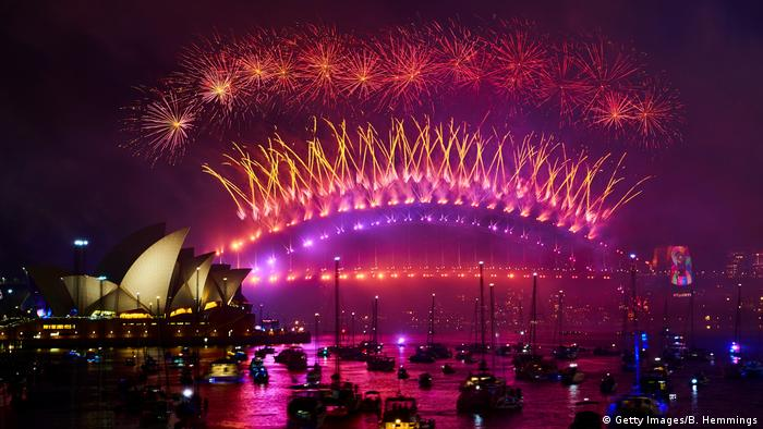 Fireworks explode above Sydney Harbor as boats sit on the water (Getty Images/B. Hemmings)