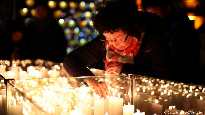 A woman bends over candles (Getty Images/C. Sung-Jun)