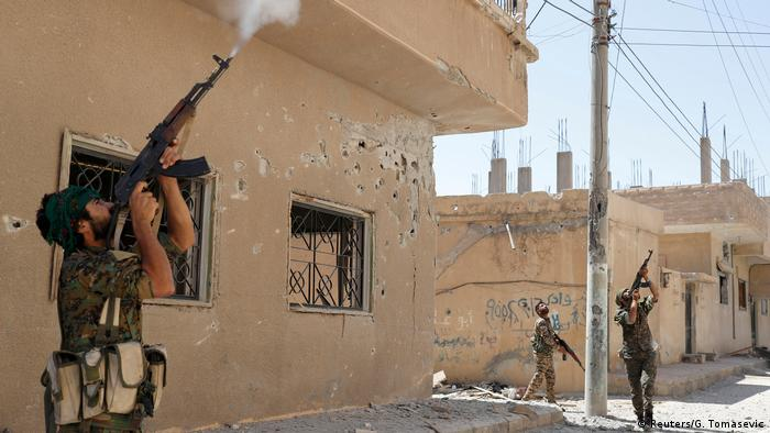 Kurdish rebel fighters fire at an IS drone
