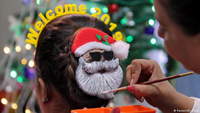 A make-up artist paints the hair of a woman into a shape of Santa Claus (Reuters/A. Dave)