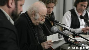 Hilsenrath reads a passage from a book into a microphone