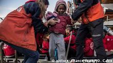 28.12.2018, Spanien, Algeciras: Mitarbeiter der spanischen NGO Proactiva helfen einem Kind von Bord des spanischen Rettungsschiffs Open Arms, nachdem es am 21.12. im zentralen Mittelmeer mit anderen Migranten gerettet wurde. Andere europäische Länder wie Italien, Malta oder Griechenland schlossen ihre Häfen für das Schiff, nur Spanien erklärte sich bereit, die Menschen aufzunehmen. Foto: Olmo Calvo/AP/dpa +++ dpa-Bildfunk +++ |