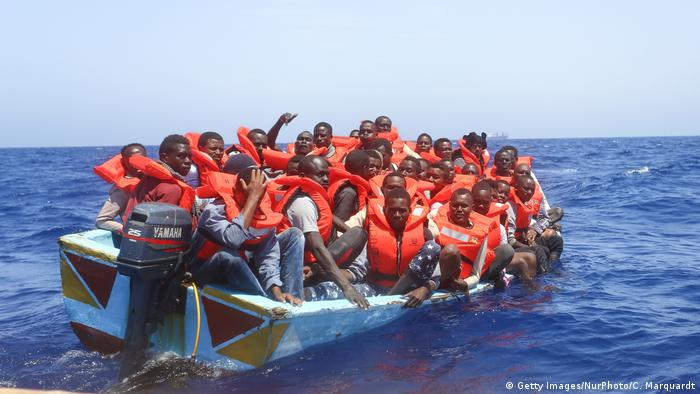 Migrants traveling on an overcrowded wooden boat in the Mediterranean
