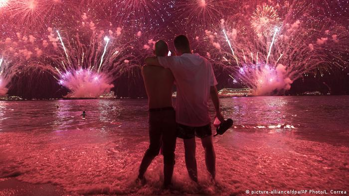 Two men watch a firework show in Rio de Janeiro at New Year's 2019