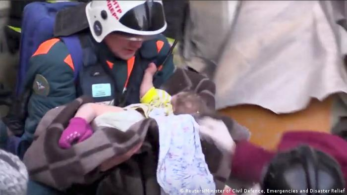 A rescuer carries a 11-month-old child found alive in the rubble of a Russian apartment block that partially collapsed after a suspected gas blast