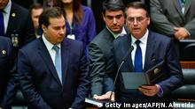 Jair Bolsonaro (R) swears in as Brazil's new President, next to Brazilian Lower House President Rodrigo Maia (L), during his inauguration ceremony, at the Congress in Brasilia on January 1, 2019. - Bolsonaro takes office with promises to radically change the path taken by Latin America's biggest country by trashing decades of centre-left policies. (Photo by NELSON ALMEIDA / AFP) (Photo credit should read NELSON ALMEIDA/AFP/Getty Images)