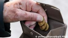 An elderly person takes the last few coins out of a wallet (picture-alliance/dpa/S. Pilick)